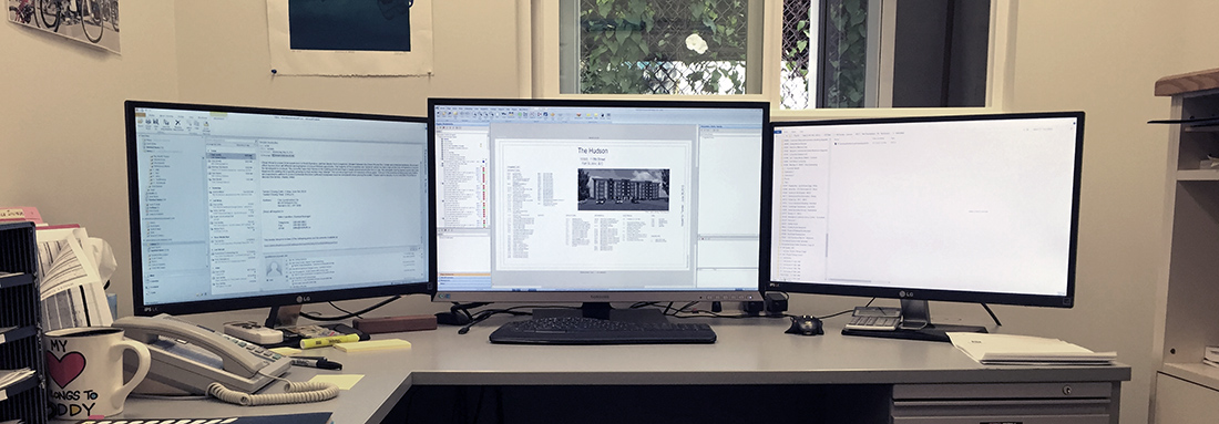3 computer screens on a desk